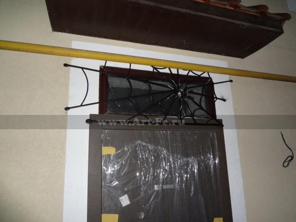 Кованая оконная решетка над дверью, паутина и ПАУК